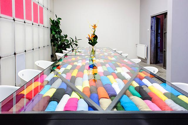 OP Tiger - OP TIGER je poměrně mladá firma s majiteli ve středním věku, proto naše pracovní prostředí působí svěže a minimalisticky. Zasedačka, kterou prezentujeme, vystihuje částečně činnost, kterou se zabýváme (tedy sítotiskové šablony pověšené na zdi, textil zakomponovaný v jednacím stole). Nepřehlédnutelný je také showroom textilních produktů posazený na kovových podstavcích s velkými okny s posuvnými dveřmi. Pod tímto objektem je klasický open space se stoly jednotlivých zaměstnanců kanceláře. Kancelář je z obou stran obklopena výrobou, oboustranné přepažení prostoru je také prosklené.