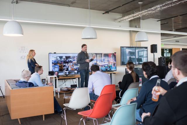 Andy Payne ukazuje novinářům výsledky práce svého týmu Cisco Emerge a na bílé stoličce je týmový asistent Monica